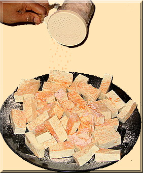 Seasoning tofu with a mixture of flour, salt & chili powder